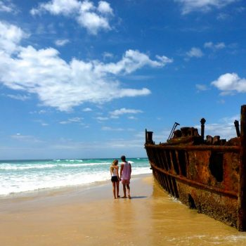 A man and a woman stand on a beach on Fraser Island
