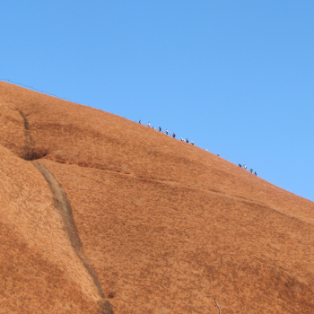 Climbers look tiny as they hike up Uluru