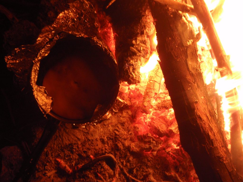 Damper bread bakes in the coals on a fire